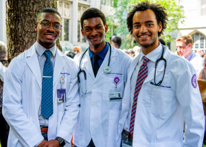 Three men in white coats smiling. Two of the men have stethoscopes draped over their shoulders.