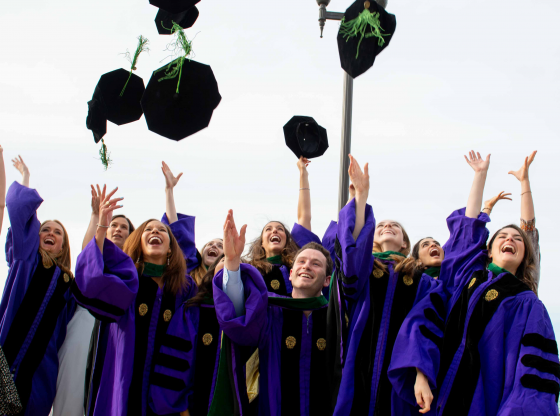 2019 Feinberg MD graduates throwing caps in the air.