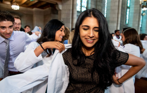 Group of people in a church. Woman in foreground is helped into a white coat.