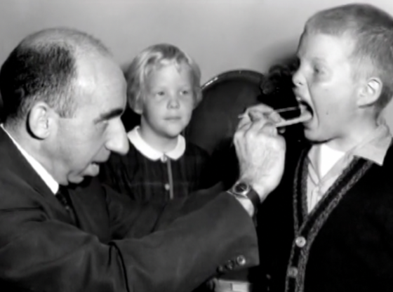 Dr. Stamler examining the throat of a young boy while a young girl watches.