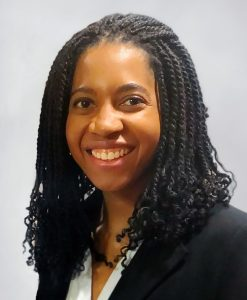 Woman smiling. She has long braids and wears a black suit jacket and white blouse.