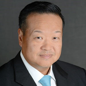 Headshot of man wearing a dark suit jacket and a blue necktie.